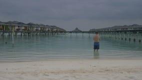 Человек приходит в океан, стоя перед виллами воды Белый песчаный пляж Мальдивов видеоматериал