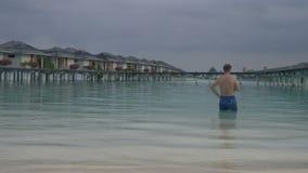 Человек приходит в океан, стоя перед виллами воды Белый песчаный пляж Мальдивов акции видеоматериалы