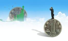 Человек при бинокли стоя на гигантских юанях смотря верхнюю диаграмму ища финансовый успех в китайских рынках стоковое фото