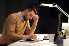 Человек при блокнот работая на офисе ночи стоковые фотографии rf