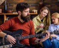 Человек при борода битника играя гитару на партии коллежа Музыкант репетируя новую песню Бородатый человек развлекая 2 белокурое Стоковая Фотография RF