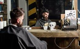 Человек при борода покрытая с черной накидкой сидит в стуле парикмахеров перед зеркалом Битник с бородой ждет стоковое фото