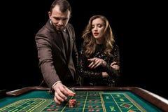 Человек при женщина играя рулетку на казино Наркомания к стоковые изображения
