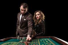 Человек при женщина играя рулетку на казино Наркомания к стоковые изображения rf