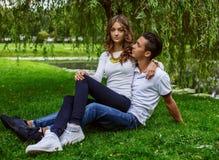 Человек при женщина ослабляя на зеленой траве в парке Стоковое Фото