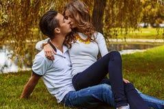 Человек при женщина ослабляя на зеленой траве в парке Стоковая Фотография