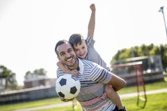 Человек при ребенок играя футбол на поле Стоковая Фотография