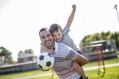 Человек при ребенок играя футбол на поле Стоковое Изображение RF