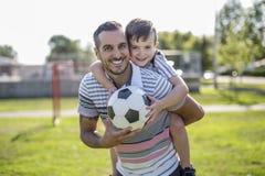 Человек при ребенок играя футбол на поле Стоковая Фотография RF