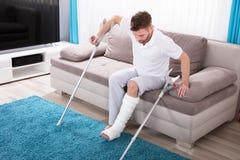 Человек при сломанная нога получая вверх от софы стоковая фотография