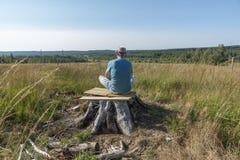 Человек при чонсервная банка сидя на дереве и делая йогу стоковые изображения rf