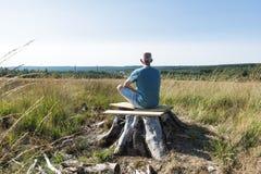 Человек при чонсервная банка сидя на дереве и делая йогу стоковое изображение rf