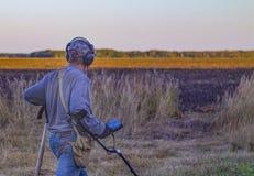 Человек при электронный прибор металлоискателя работая на предпосылке outdoors Фотография конца-вверх искать процесс стоковое фото