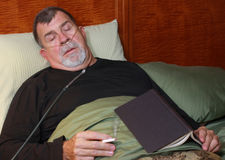Человек при Cannula кислорода куря в кровати Стоковые Фото