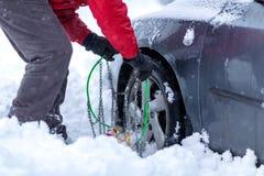 человек пробует положить цепи снега на автошины стоковые изображения