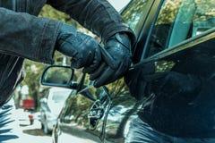Человек пробует сломать замок автомобиля с отверткой стоковое изображение rf