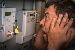 Человек проверяет метр электричества - дорогое concep электричества стоковое фото