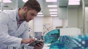 Человек проверяет работу прибора лаборатории с таблеткой стоковое изображение