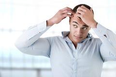 Человек проверяя волосяный покров Стоковая Фотография
