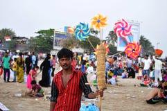 Человек продавая Multi Pinwheel цвета стоковые изображения