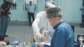 Человек продает серебряные блюда в восточном рынке Tableware Дагестана винтажный античный Баки, вазы, баки, плиты, медь и сток-видео