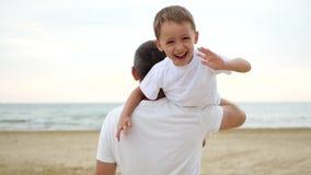 Человек продолжает его плечо счастливый смеясь мальчик который развевает его руки Концепция семьи и на открытом воздухе воссоздан видеоматериал