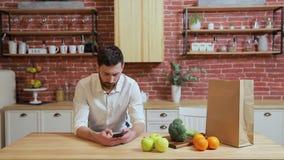 Человек просматривая на кухне мобильного телефона дома Красивый молодой человек просматривая на усмехаться смартфона счастливый акции видеоматериалы