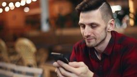 Человек просматривая на мобильном телефоне видеоматериал