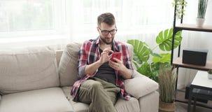 Человек просматривая социальные средства массовой информации используя мобильный телефон на софе сток-видео