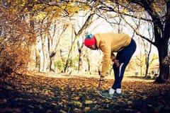 Человек протягивая ноги после тренировки сезон путя пущи падения осени стоковое фото