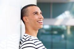 Человек профиля счастливый молодой полагаясь против белой стены стоковая фотография
