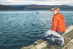 Человек путешественника сидит на пристани озера горы Стоковая Фотография RF