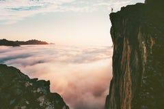 Человек путешественника стоя на скале края над облаками стоковое изображение rf