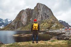 Человек путешественника с желтым рюкзаком нося красное положение шляпы на предпосылке горы и озера Образ жизни перемещения стоковые изображения rf