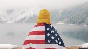 Человек путешественника с флагом положения Америки в покрытых снег горах около красивого озера Hiker смотря