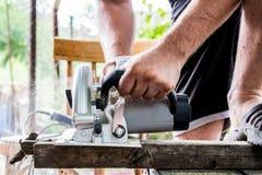 Человек работает с его руками и инструментом конструкции Электрическо увидел Работа на деревянных досках Отрезать материалы стоковое фото rf