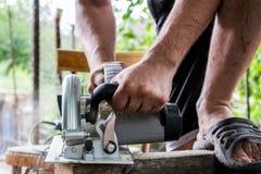 Человек работает с его руками и инструментом конструкции Электрическо увидел Работа на деревянных досках Отрезать материалы стоковое фото