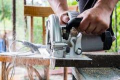 Человек работает с его руками и инструментом конструкции Электрическо увидел Работа на деревянных досках Отрезать материалы стоковое изображение