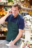 Человек работая в florist стоя на счетчике стоковое фото rf