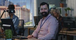 Человек работая на его столе в центре телефонного обслуживания