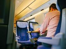 Человек работая на компьтер-книжке в скором поезде Стоковое Изображение