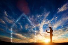 Человек работая на компьтер-книжке на заходе солнца Домашний символ Стоковые Фото