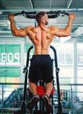 Человек работая на прессе руки на предпосылке спортзала Профессиональное оборудование спортзала Тренировка, разминка, концепция к стоковые фото