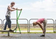 Человек работая на эллиптических тренере и женщине Стоковое Изображение RF