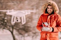 Человек работая трутня с дистанционным управлением во время холодного зимнего времени стоковое фото rf