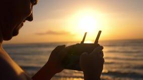 Человек работая трутня с дистанционным управлением Трутень вертолета Quadro летая над океаном захода солнца движение медленное 38 видеоматериал