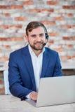 Человек работника офиса, с наушниками на голове, сидя на столе с компьтер-книжкой и усмехаться Стоковая Фотография