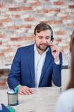 Человек работника офиса с наушниками сидит на столе и работает говорить в микрофон наушников Стоковое фото RF