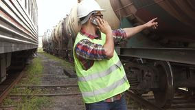 Человек работник железной дороги, в зеленой куртке и шлеме на предпосылке поезда акции видеоматериалы