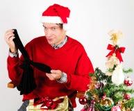 Человек развертывая подарок рождества Стоковые Фото